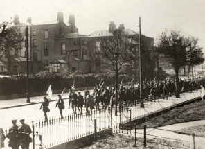 Volunteers from the 3rd Battalion marching down Grand Canal Street Lower under escort carrying their weapons and a flag after their surrender at Boland's Bakery. A white 'x' has been marked above the head of Éamon de Valera, commandant of the 3rd Battalion. Image: National Library of Ireland